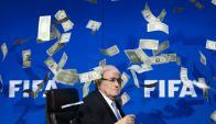Blatter, presidente de la FIFA, bajo una lluvia de dólares falsos tras ser acusado de corrupción. Foto: AFP.
