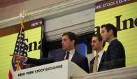 Integrantes de la empresa hacen sonar la campana. Foto: AFP