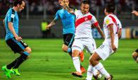 Paolo Guerrero saca el remate ante la marca de Godín. Foto: AFP