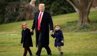 Trump: el presidente de la mano de sus dos nietos. Foto: Reuters