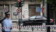 El auto del exprimer ministro Papademos custodiado tras explosión. Foto: Reuters