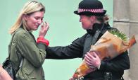 Una londinense le entrega flores a una policía en recuerdo de las víctimas. Foto: AFP
