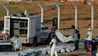 Funcionarios policiales retiran los cuerpos de los presos fallecidos. Foto: AFP