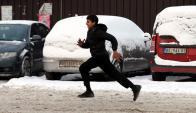 Un refugiado corre hacia un almacén abandonado para protegerse del frío. Foto: EFE