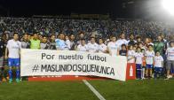 Los jugadores de Nacional y Danubio posaron con la pancarta en la previa de su partido por la segunda fecha. Foto: Ariel Colmegna