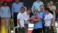 El presidente Santos y Timochenko con un bebé en brazos. Foto: AFP