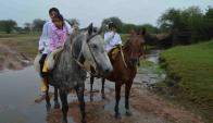 José (9 años), Isidro (6) y Rocío (4 años) llegan bastante mojados al arroyo que los separa de la escuela. Foto: D. Rojas