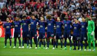 Los jugadores del Manchester United en el minuto de silencio en honor a las víctimas. Foto: EFE