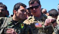 Un soldado de las YPG kurdas junto a un militar estadounidense. Foto: AFP.