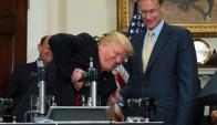 Trump prueba una máquina para aplastar botellas de vidrio. Foto: AFP