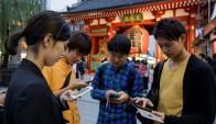 Jóvenes japoneses juegan a Pokémon Go. Foto: EFE.