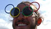 Un voluntario de los Juegos Olímpicos con unos lentes de sol con los Anillos Olímpicos. Foto: AFP