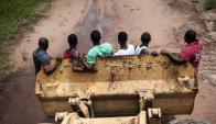 Cuatro jóvenes son transportados por una excavadora en Nigeria. Foto: AFP.