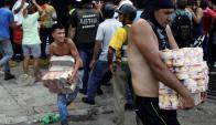 Venezolanos se llevan alimentos tras un saqueo en un súper de Caracas. Foto: Reuters