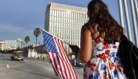 Una mujer cubana sostiene una bandera de Estados Unidos frente a la embajada en La Habana. Foto: EFE