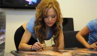 Jessica Zunino firmando calendarios de la marca Feyvi