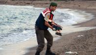 Niño muerto siendo recogido por un gendarme turco. Foto: Reuters.