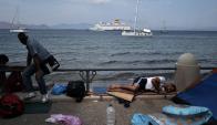 Refugiados sirios en la isla de Kos, observan el arribo de un barco. Foto: AFP