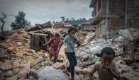 Dos niñas tapan su nariz al caminar entre escombros llenos de cadáveres. Foto: AFP