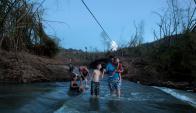 Habitantes de San Lorenzo, cruzan a pie un río, después que el puente fue destruido.. Foto: Reuters