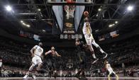 Kevin Durant la hunde ante la mirada de LeBron James en el duelo entre Cleveland y Warriors. Foto: AFP