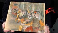 El cuadro requisado por la policía, Las coristas de Degas sostenido por un agente. Foto: AFP