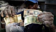 Un ciudadano muestra billetes de uno, cinco y veinte pesos emitidos por el Banco Central. Cuba unificará sus monedas. Foto: AFP.