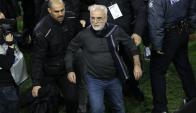 Ivan Savvidis, presidente del PAOK, abandona el campo de juego rodeado de guardaespaldas. Foto: EFE