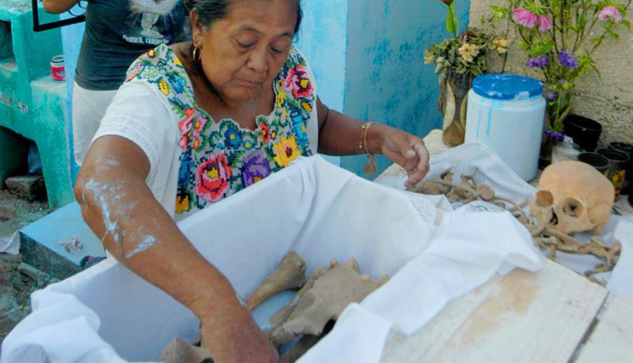 Es una tradición sacar los huesos de los nichos para limpiarlos. Foto: EFE