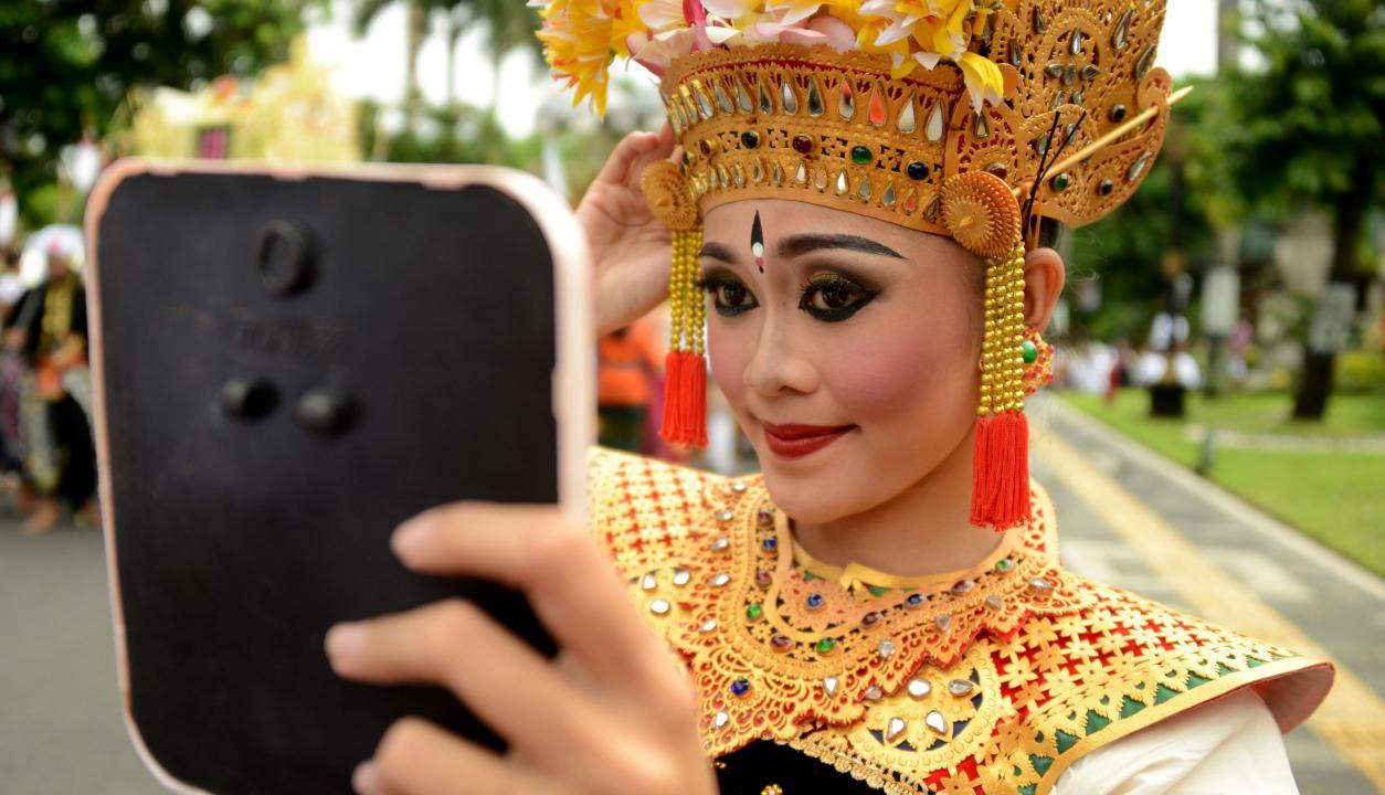 Joven se prepara para las celebraciones de cambio de año en Bali. Foto: AFP