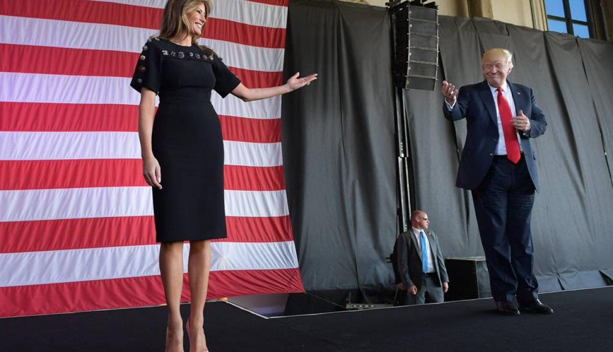 Donald Trump y Melania interactuan sobre un escenario en un acto con militares. Foto: AFP