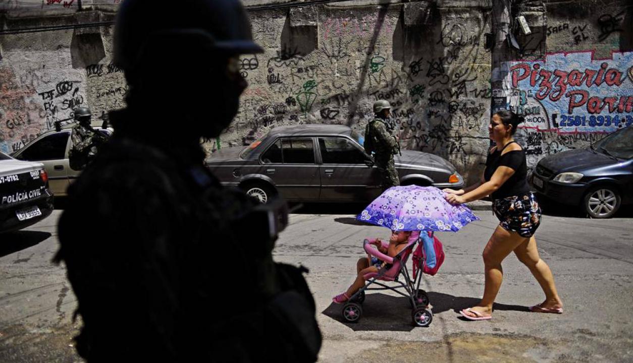 Una mujer pasa con su carro frente a un policía en una de ellas. Foto: AFP
