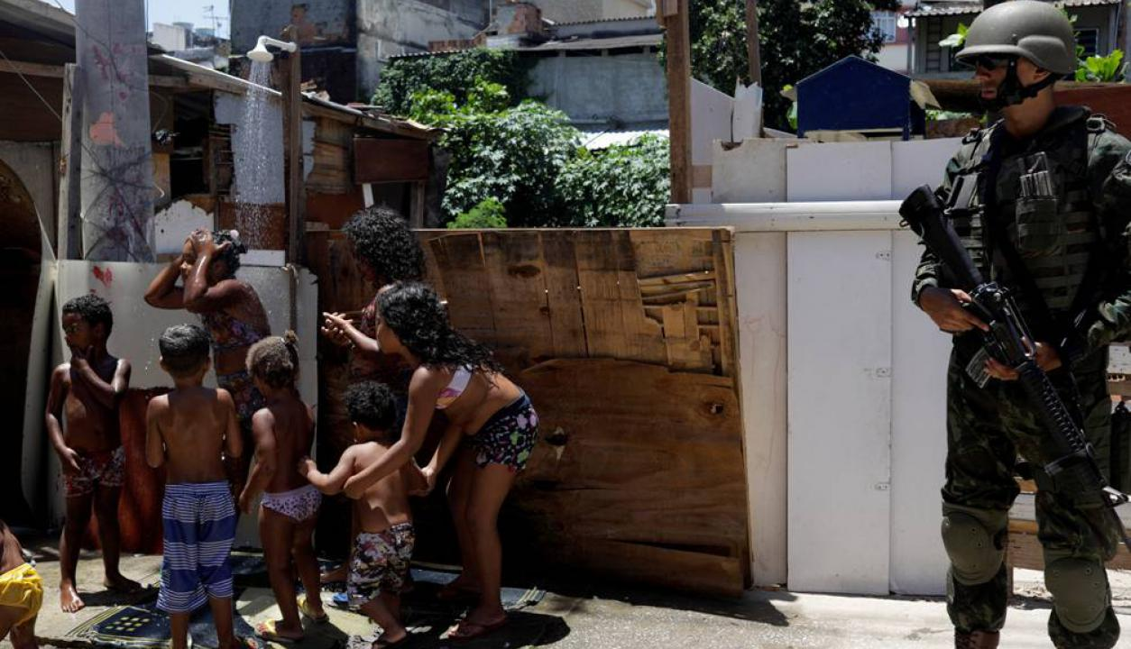 Algunos niños se refrescan en una ducha en la vereda mientras el operativo se desarrolla. Foto: AFP