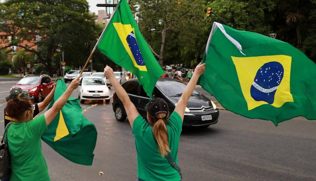 Dos mujeres celebran con banderas brasileñas la decisión tomada por la Justicia. Foto: AFP