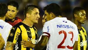 El cruce entre Cristian Rodríguez y Diego Polenta en el clásico de verano Peñarol vs. Nacional. Foto: Gerardo Pérez