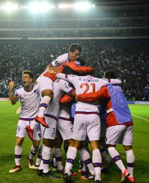 Celebración. El abrazo gigante de los jugadores de Nacional tras el gol de Matías Zunino mientras Fucile y Romero festejan con la hinchada. Foto: Darwin Borrelli