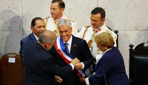 El presidente del senado y la saliente Bachelet le ponen la banda presidencial. Foto: Reuters