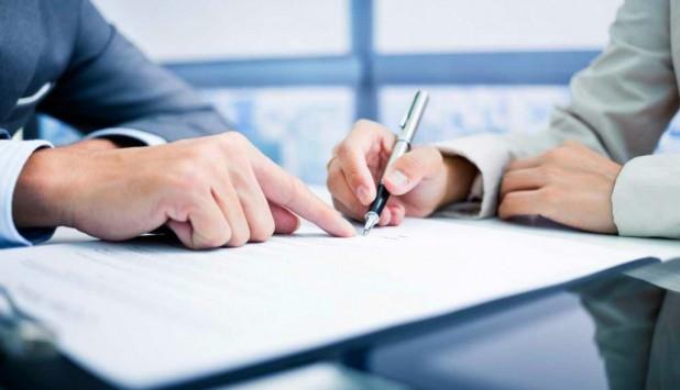 Persona firmando un documento. Foto: Archivo El País