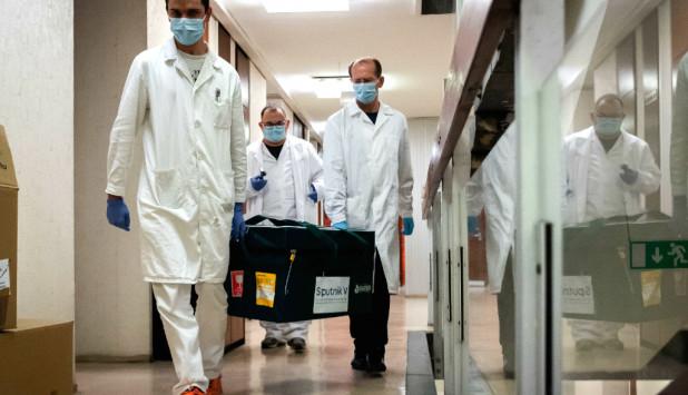 Funcionarios de salud llevan muestras de la vacuna rusa Sputnik V. Foto: Reuters